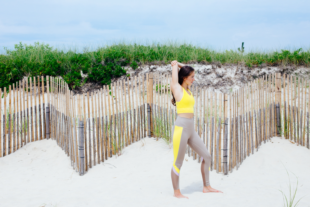 Molly aka @progresspure stretching on the beach in the hamptons wearing Alo Yoga as one of the best workout trainers on the KR Edit